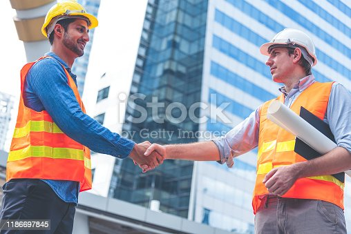 1071990712istockphoto Engineer in Yellow helmet and best greeting with warm handshake manager visiting site. Modern construction and engineering concept. Safety of work in production and construction work place. 1186697845