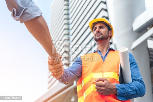 1071990712istockphoto Engineer in Yellow helmet and best greeting with warm handshake manager visiting site. Modern construction and engineering concept. Safety of work in production and construction work place. 1189758162