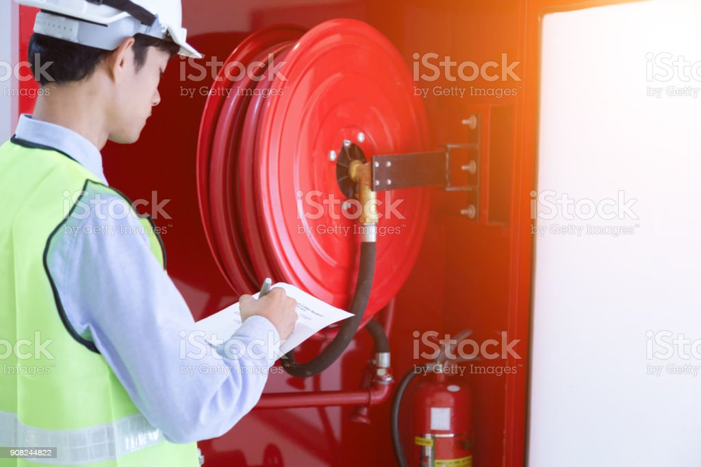 Engineer inspection Fire extinguisher and fire hose. stock photo