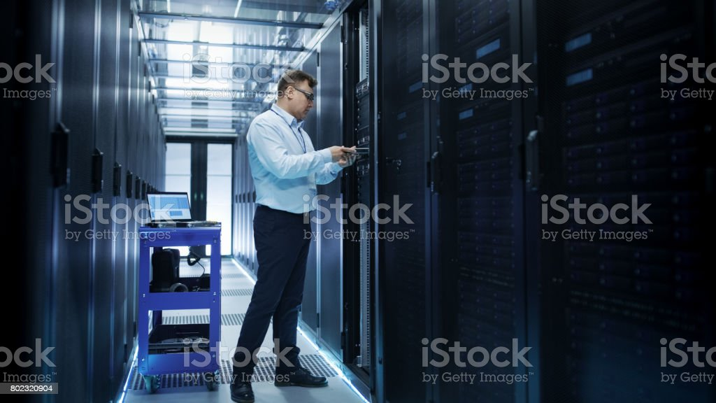 IT Engineer Installing Hard Drives into Working Rack Server. He's Working in Data Center. IT Engineer Installing Hard Drives into Working Rack Server. He's Working in Data Center. Administrator Stock Photo
