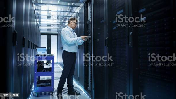 It Engineer Installing Hard Drives Into Working Rack Server Hes Working In Data Center Stock Photo - Download Image Now