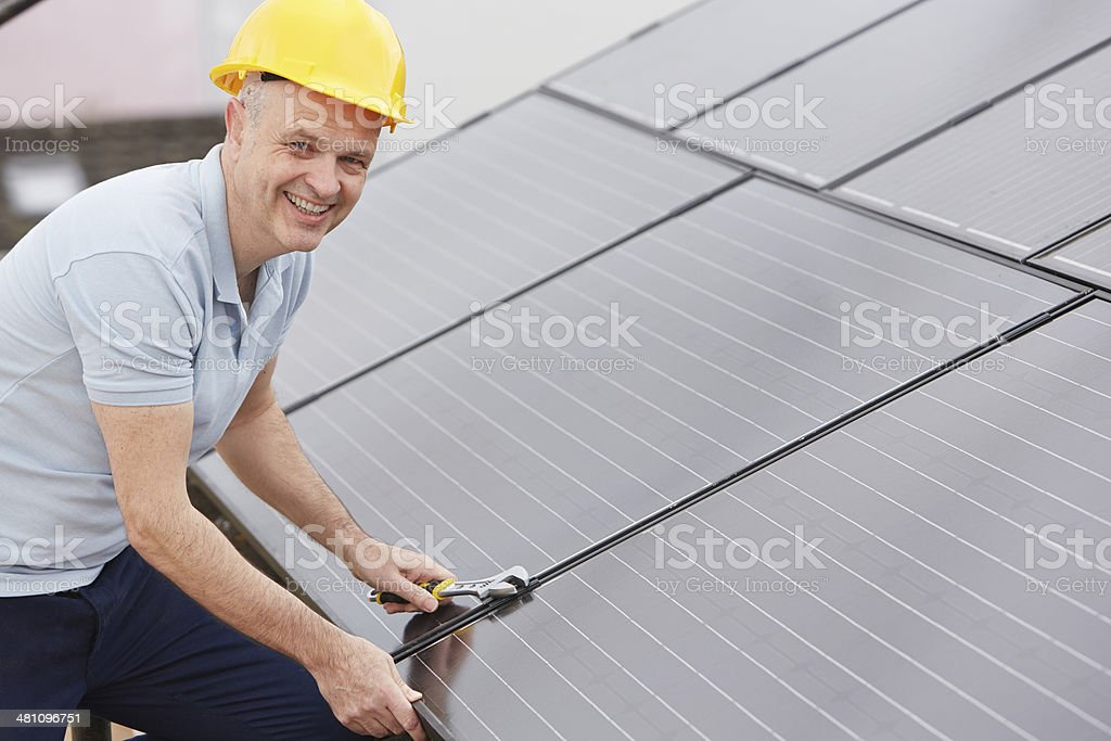 Engineer Installing Solar Panels On Roof Of House stock photo