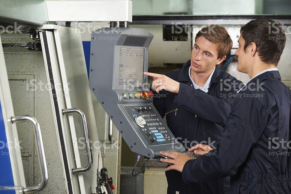 Engineer Instructing Trainee On Use Of Computerized Cutting Tool stock photo