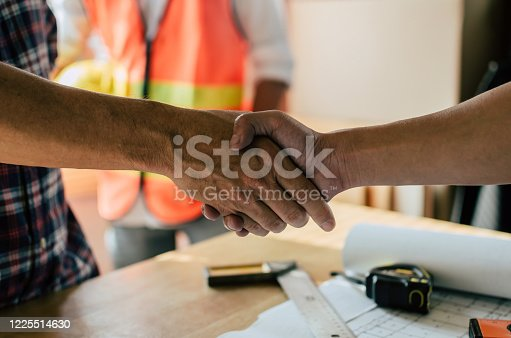 1055059750 istock photo engineer, interior designer and architect hands shaking greeting start up plan new project contract with blueprint on desk in meeting room office at construction site, partnership, contractor concept 1225514630