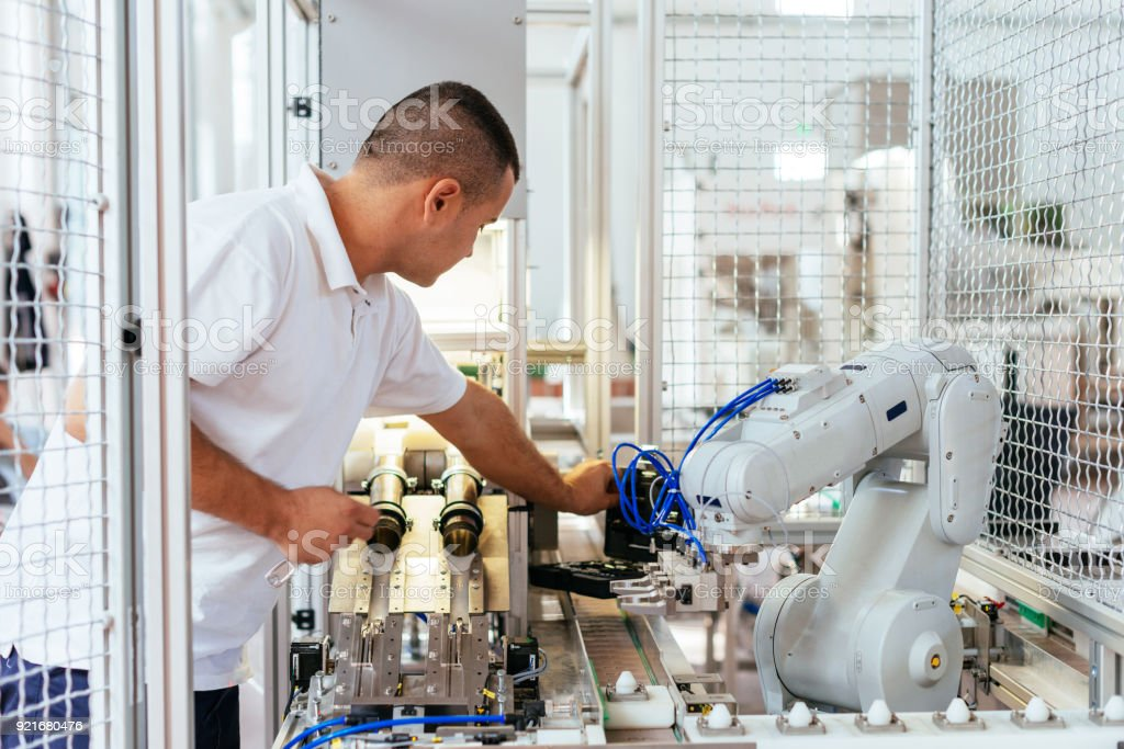 Engineer is examining modern production line robot stock photo