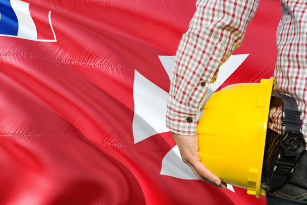 Engineer is holding yellow safety helmet with waving Wallis And Futuna flag background. Construction and building concept. stock photo
