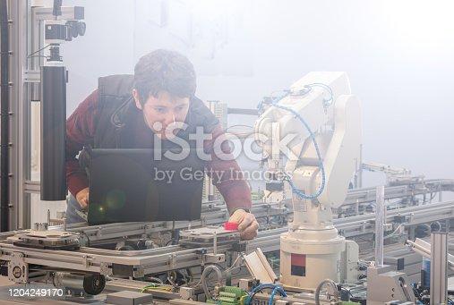 1190871157 istock photo Engineer is working on a smart factory prototype. 1204249170