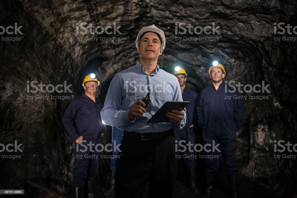 Engineer leading a group of miners stock photo