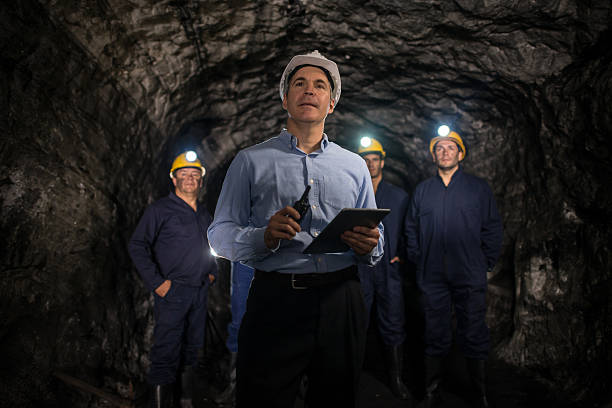 engineer leading a group of miners - 採礦業 個照片及圖片檔