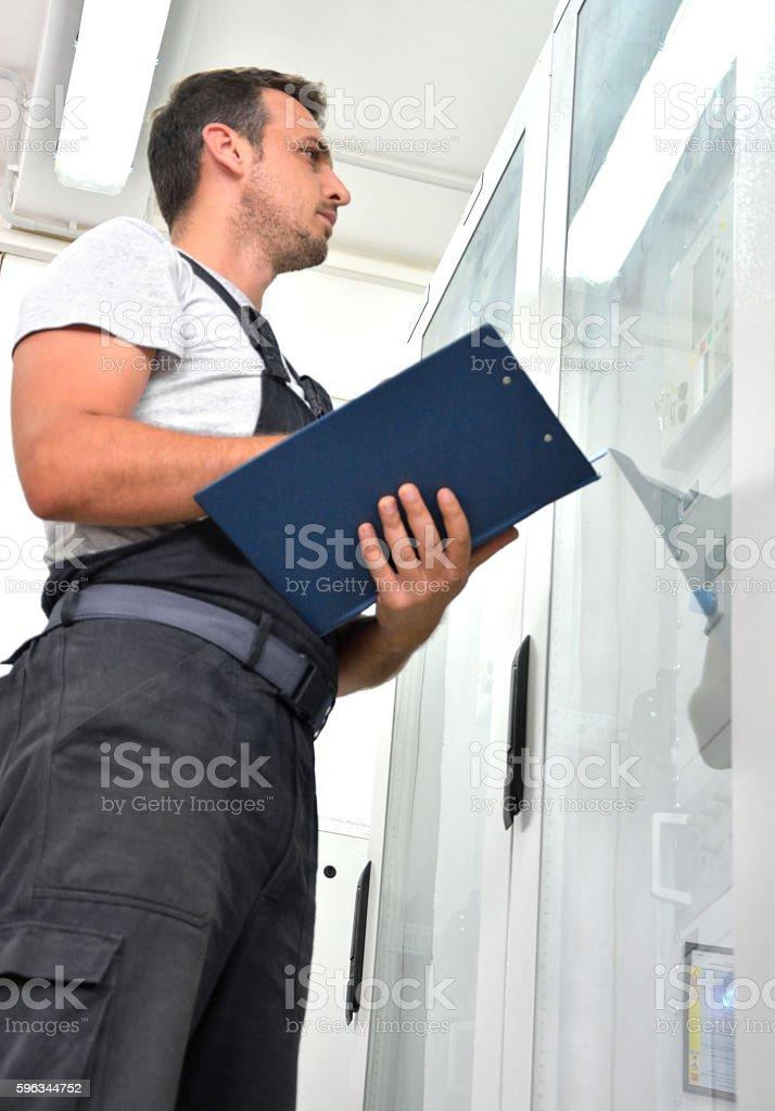Engineer Looking at Blueprints in Control Room Lizenzfreies stock-foto