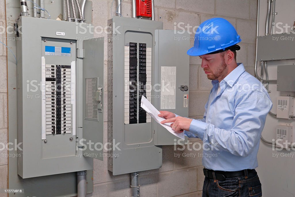 Engineer looking at file in front of control panel - Royalty-free Adult Stock Photo