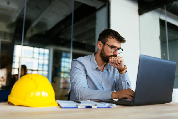 Engineer looking at laptop stock photo