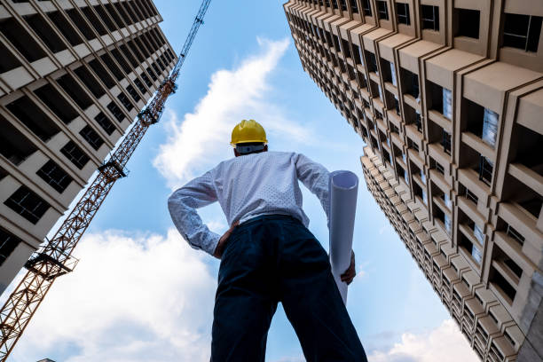 Engineer looking up the building he designed proudly stock photo