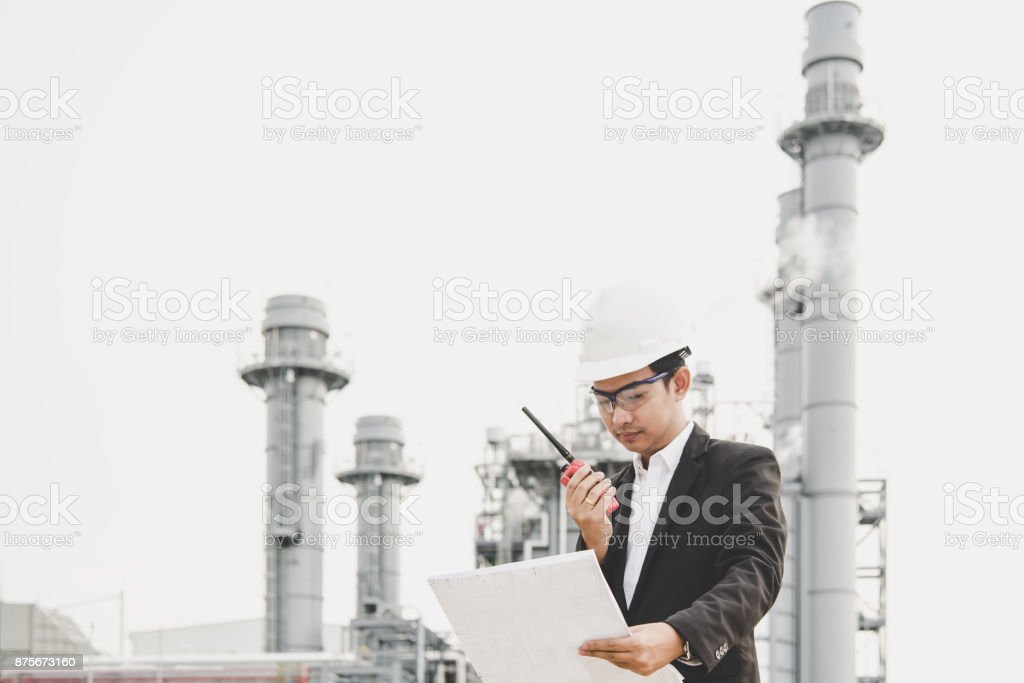 Engineer man holding white helmet and blueprint with radio for workers security control at power plant energy industry. Engineer Concept stock photo