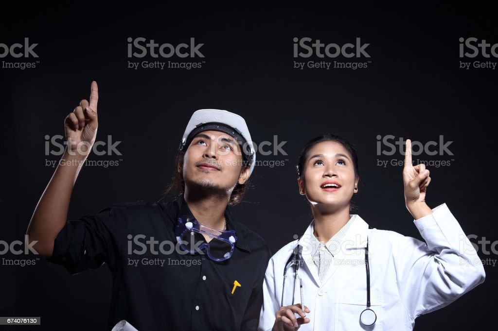 Engineer Man with safety had, goggle, vast and blueprints, stand with beautiful doctor royalty-free stock photo