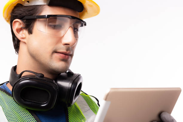 Engineer man working on digital tablet computer at worksite or industry. Handsome young industrial worker planning and thinking job on tablet. Young men get successful of business. isolated on white stock photo