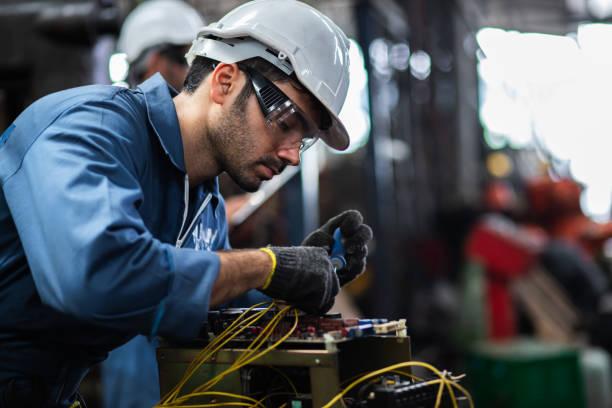 ingenieur handarbeiders die zich in een aluminiummolen bevinden en samenwerken. gebruikte professionele apparatuur. handarbeiders die samenwerken bij het meten van een elektronisch apparaat. - elektricien stockfoto's en -beelden