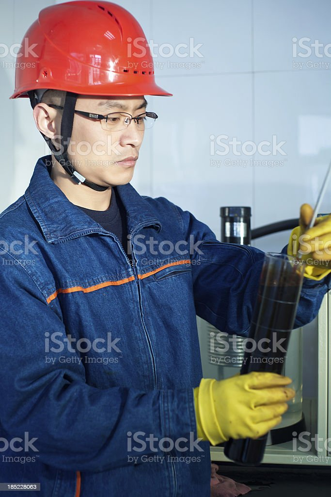 Engineer measuring the temperature of oil sample royalty-free stock photo