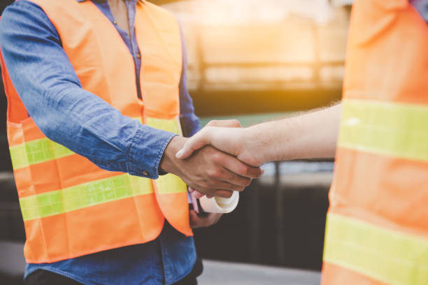 Engineer men making handshake in construction site. Employee or worker shake hands to employer man for greeting, dealing, teamwork, collaboration some project or business. They are good team stock photo