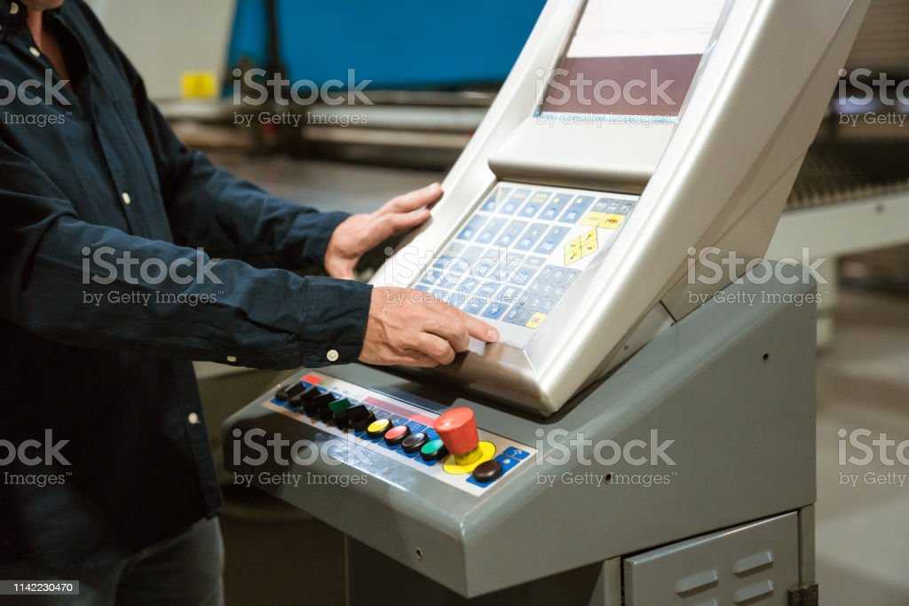 Engineer operating machinery in industry Midsection of male instructor operating puller machine. Mature engineer is working in factory. He is in casuals. 55-59 Years Stock Photo