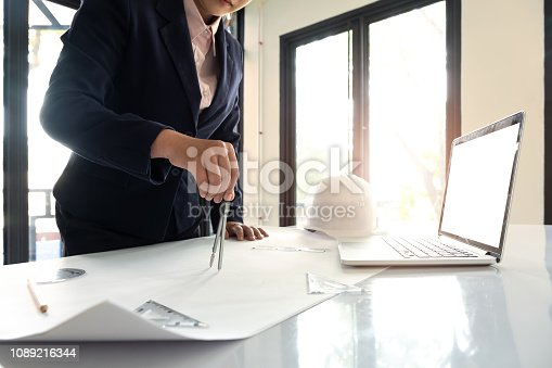 istock Engineer or Architect concept, Image of engineer drawing a blue print design building or house, An engineer workplace with blueprints, pencil, protractor and safety helmet, Industry concept 1089216344