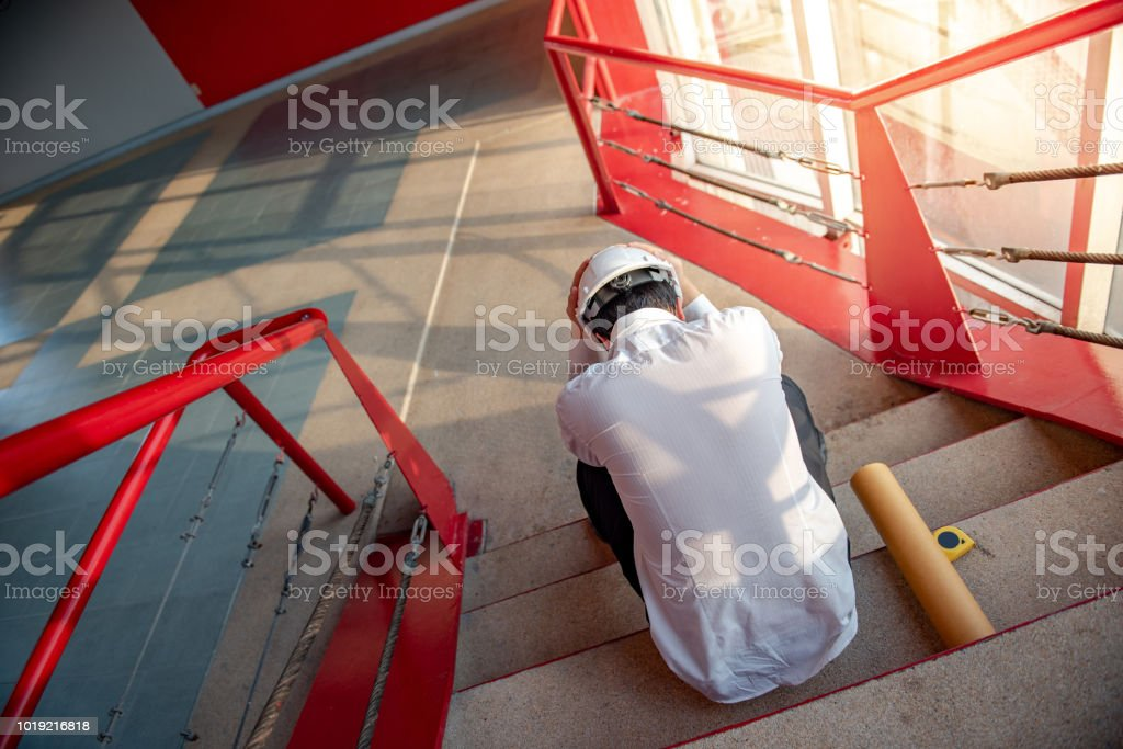 Engineer or Architect feeling tired and headache with his job. sitting on building stairs with architectural drawing on his side while wearing protective equipment safety helmet at construction site stock photo