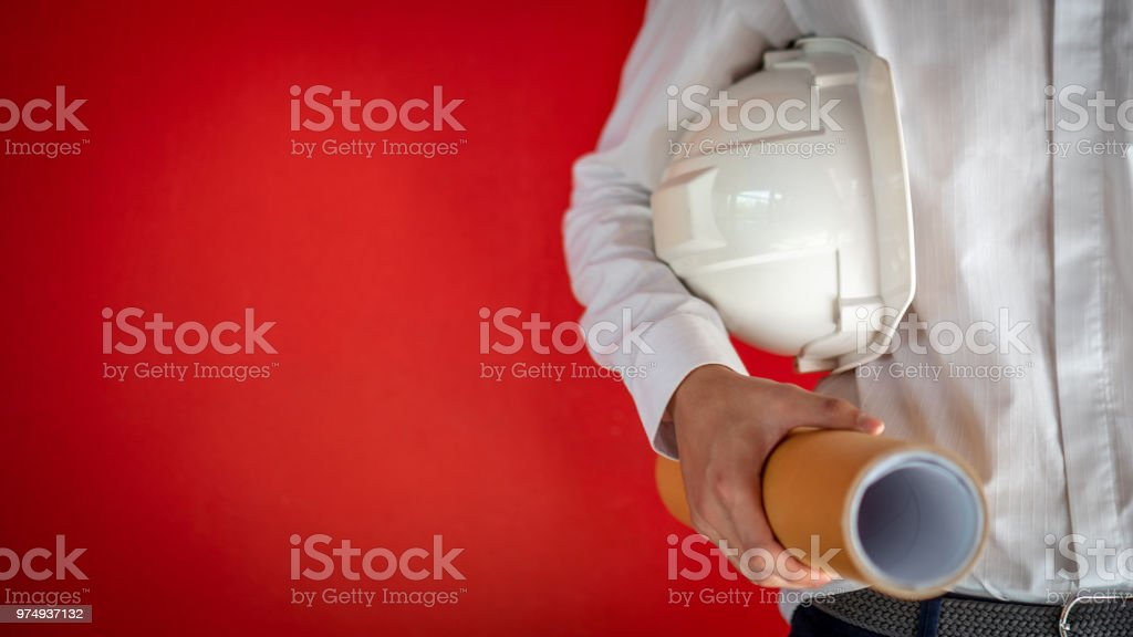Engineer or Architect holding personal protective equipment safety helmet and architectural drawing in red background. Engineering, Architecture and building construction business concepts stock photo