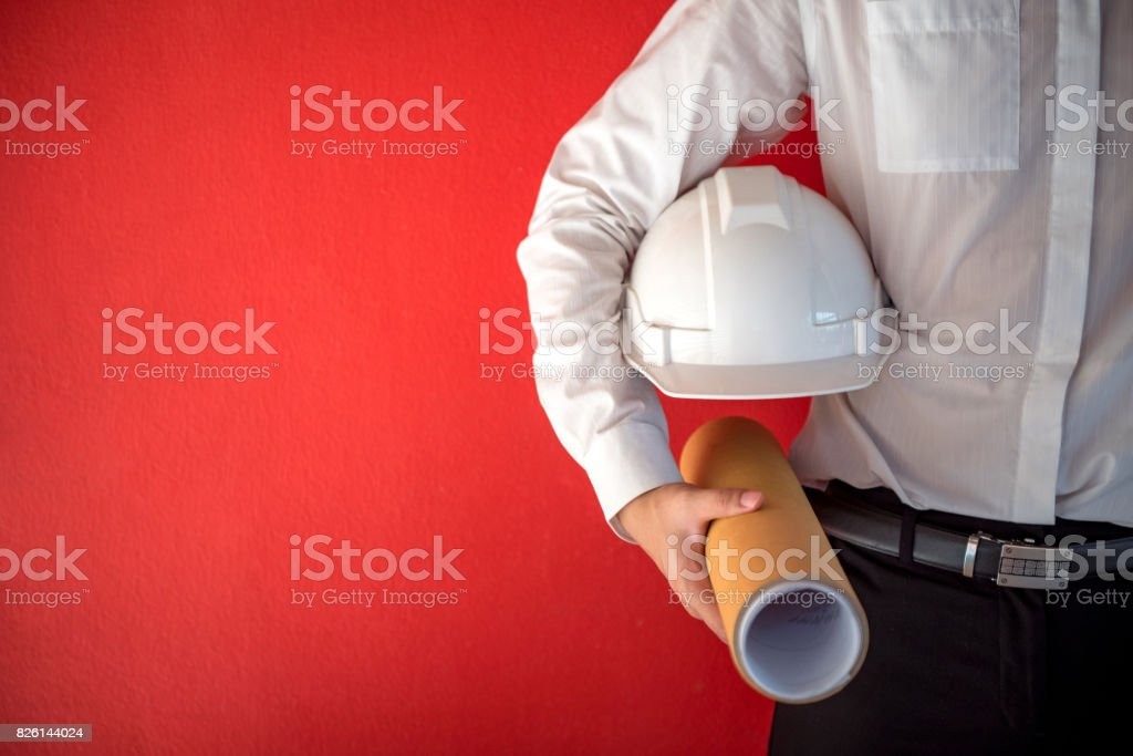 Engineer or Architect holding safety helmet and architectural drawing in red background stock photo