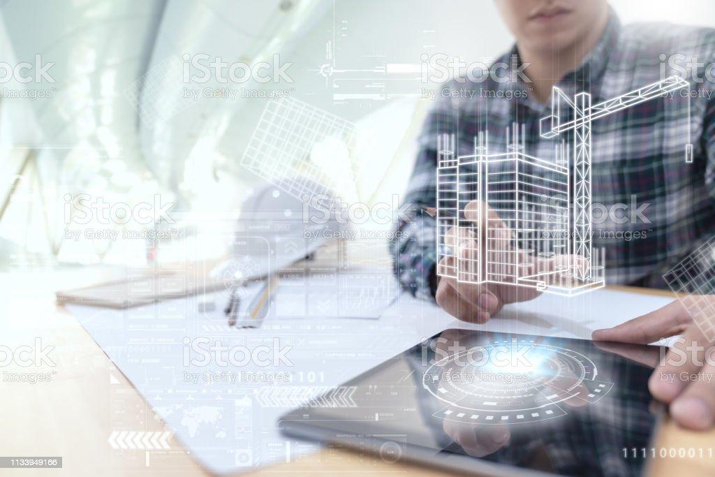 L'ingénieur ou l'architecte regardant et touchant l'interface avec la technologie virtuelle de conception de construction de réalité sur la tablette d'ordinateur au bureau moderne sur le site. Automatisation du bâtiment concept de contrôle sans fil nu - Photo de Adulte libre de droits