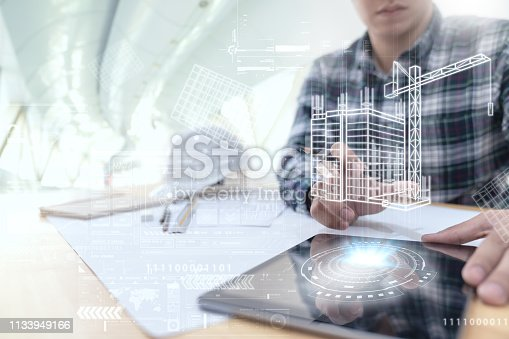 istock Engineer or Architect looking and touching interface with building design reality virtual technology on computer tablet at modern office on site . Building automation digital wireless control concept 1133949166