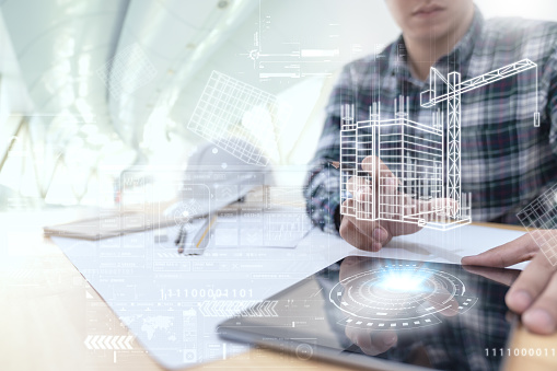 Engineer or Architect looking and touching interface with building design reality virtual technology on computer tablet at modern office on site . Building automation digital wireless control concept