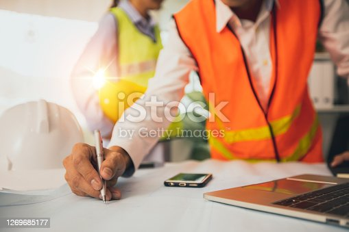 engineer or architect planning with technology concept, construction worker draw and designer on blue print and watching on laptop