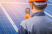 istock engineer or electrician working on  maintenance equipment at industry solar power;  engineer using thermal imager to check temperature heat of solar panel 1064082470