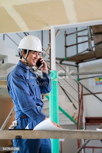 1054724700 istock photo Engineer or inspector at building construction site talking on smartphone 542945286