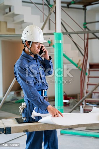 1054724700 istock photo Engineer or inspector at building construction site talking on smartphone 546187802