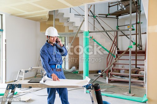 1054724700 istock photo Engineer or inspector at building construction site talking on smartphone 576607632