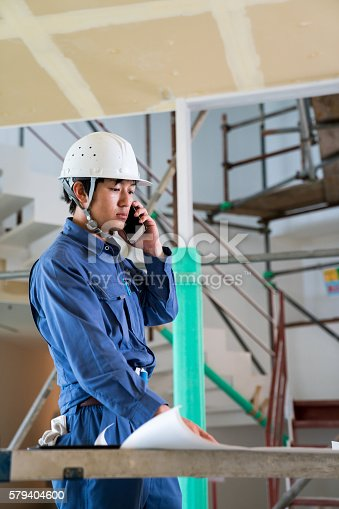 1054724700istockphoto Engineer or inspector at building construction site talking on smartphone 579404600