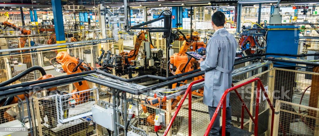 Engineer overseeing automated production process in a factory Male engineer standing on a platform with a digital tablet looking at robotic arms doing work in an automated home appliance factory. Adult Stock Photo