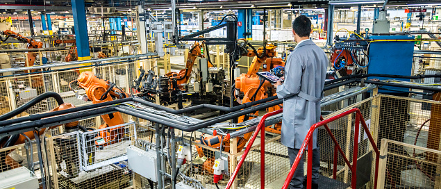 Engineer Overseeing Automated Production Process In A Factory Stock Photo - Download Image Now