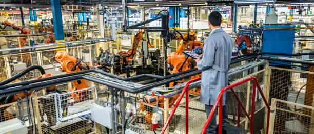ingenieur toezicht op geautomatiseerde productieproces in een fabriek - robot engineer stockfoto's en -beelden