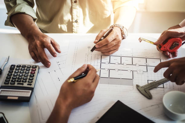 engineer people meeting working and pointing at a drawings in office for discussing. Engineering tools and construction concept. stock photo