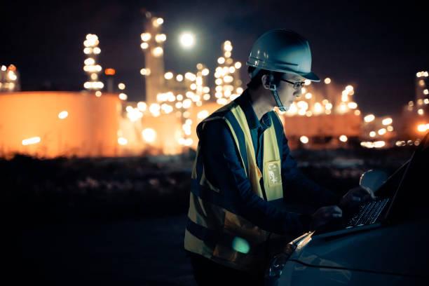 Ingeniero petroquímico asiático el hombre trabaja tarde y duro con la tableta inteligente dentro de la fábrica de petróleo y gas industria de la refinería por la noche - foto de stock