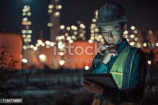 Engineer Petrochemical Asian man work late and hard with Smart tablet Inside the Refinery oil and gas Industry Factory at night
