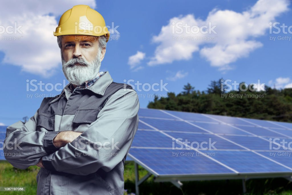 Senior engineer standing in front of solar panels
