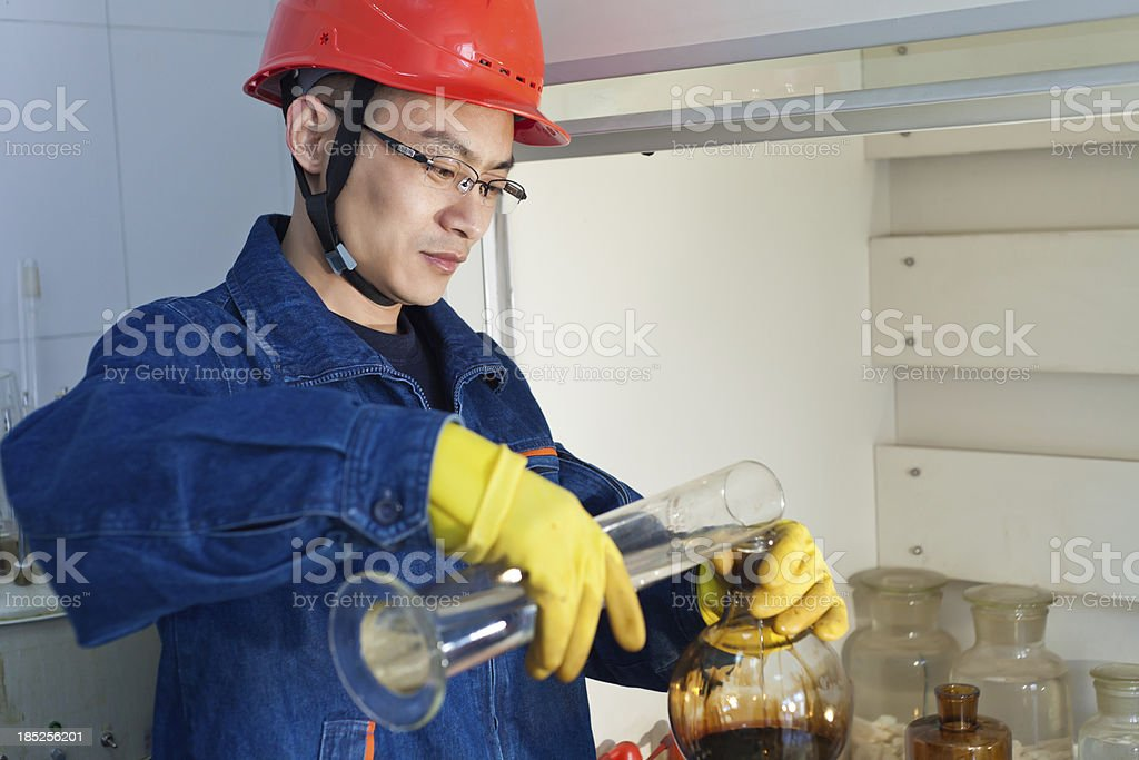 Engineer pouring the liquid into experimental flask royalty-free stock photo