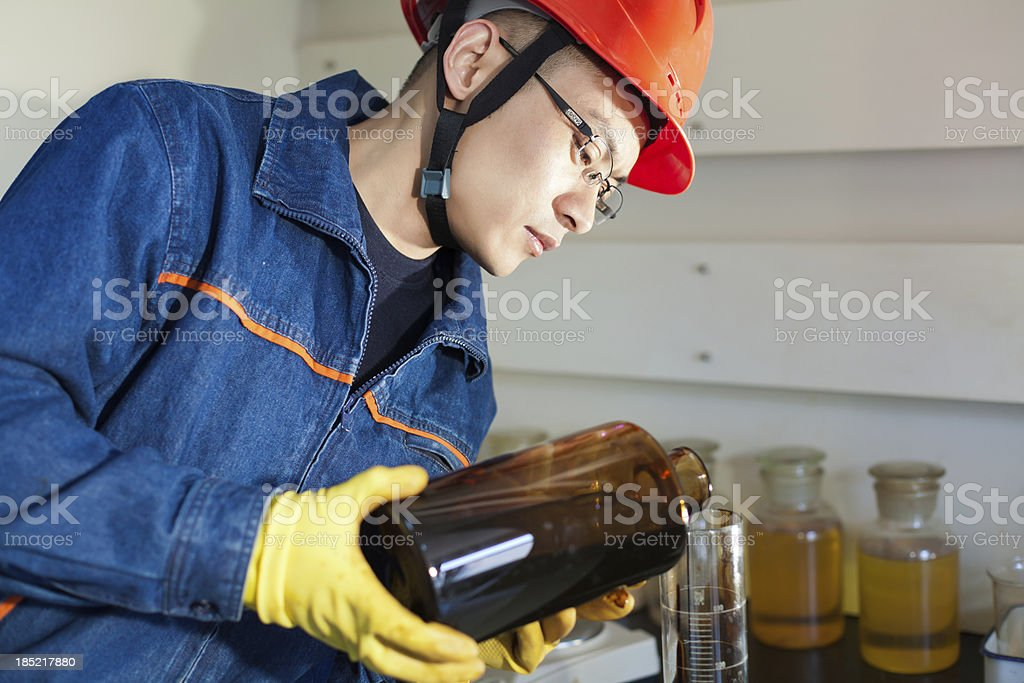 Engineer pouring the oil sample into experimental test tube royalty-free stock photo