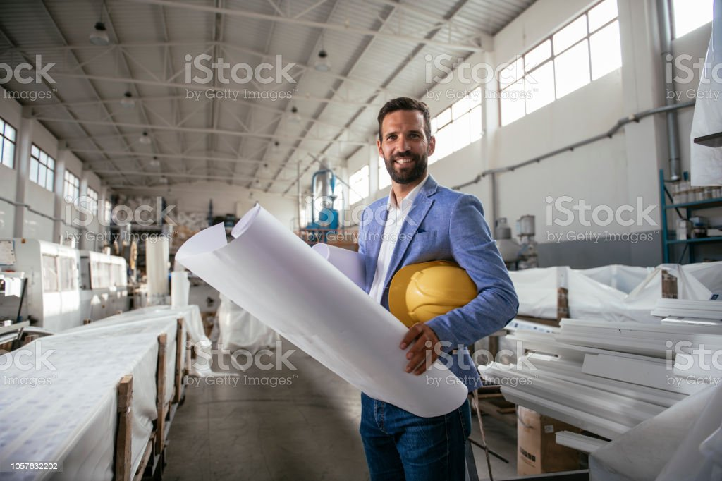Engineer reading blueprint in factory . Shadow DOF. Developed from...