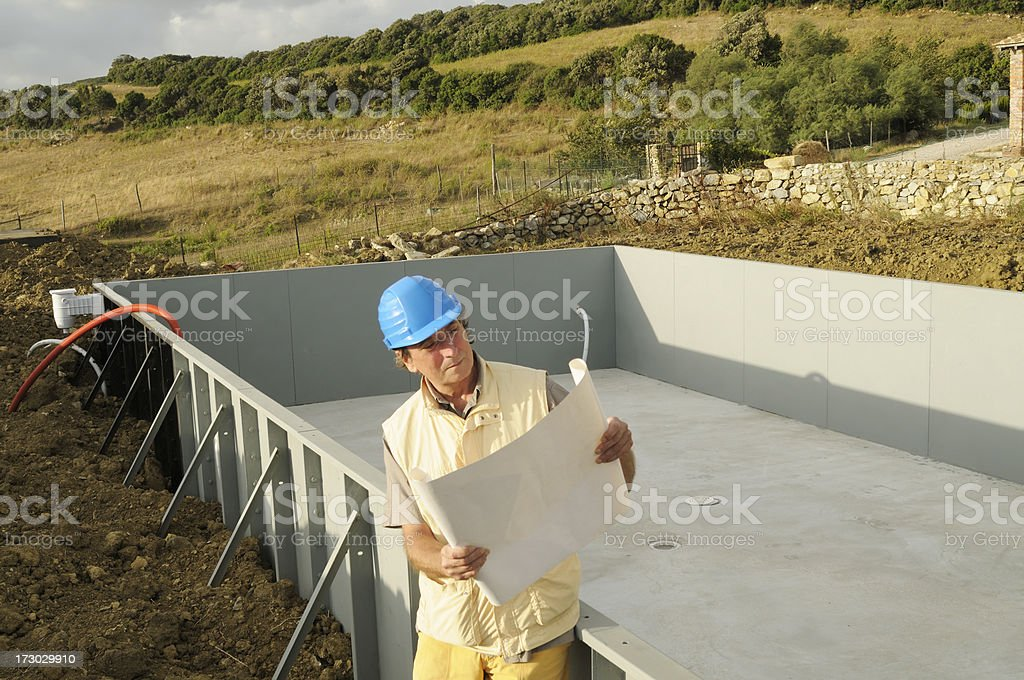 Engineer reading plan of a new swimming pool royalty-free stock photo