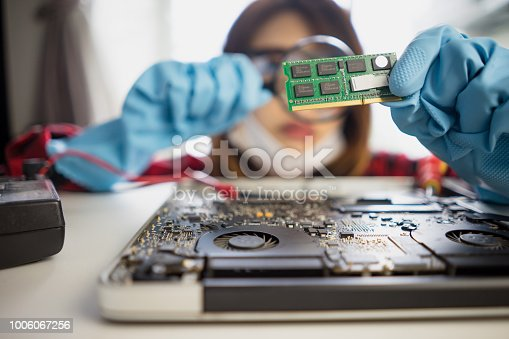 Engineer repairs laptop support fixing notebook computer. IT woman using magnifying glass installs equipment CPU, RAM Electronic technology development renovation repairing computer Hardware.