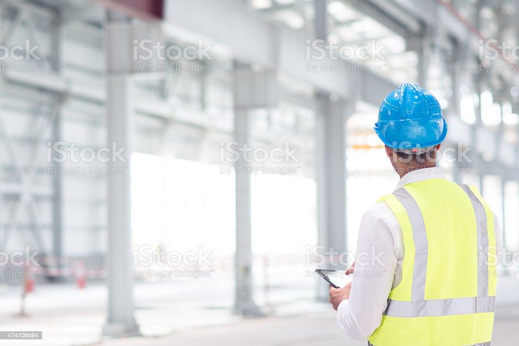Ingenieur überprüft die Pläne für Baustelle auf tablet PC – Foto